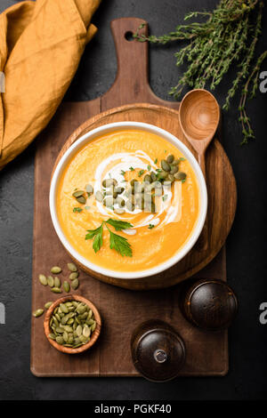 Pumpkin soup in bowl garnished with cream and pumpkin seeds. Top view. Autumn fall comfort food. Cream of pumpkin squash soup - Stock Photo