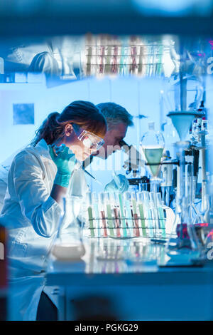 Health care researchers working in life science laboratory. Young female research scientist and senior male supervisor preparing and analyzing microsc - Stock Photo