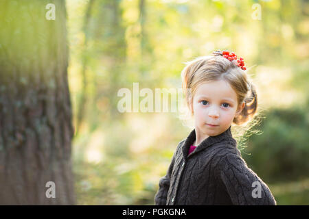 cute girl in nature with beautiful hairstyle with rowan berries.Dreamy young blonde girl hold in hands Rowan berries and look out. Autumn park.happy autumn.Copy space - Stock Photo