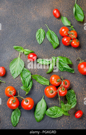 a lot of scattered green fresh basil leaves and cherry tomatoes on a dark rusty old background, close up  Top view, copy space - Stock Photo