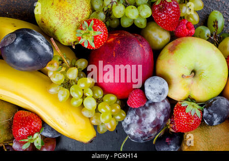 many different mixed seasonal ripe juicy fruits on dark background , concept of healthy and proper nutrition, snack, top view, copy space - Stock Photo