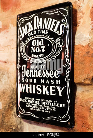 LONDON, UK - AUGUST 31, 2018: Jack Daniels retro vintage steel display plate on brick wall in pub. - Stock Photo