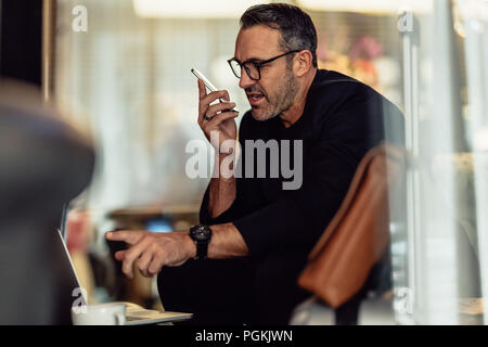 Mature businessman talking on phone while looking at laptop. CEO working while sitting in hotel foyer. - Stock Photo
