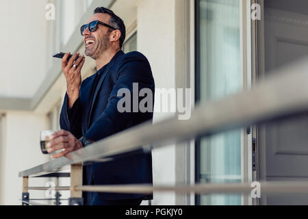 Successful mature businessman standing in hotel room balcony talking on phone. Cheerful man in suit making a call from hotel room. - Stock Photo