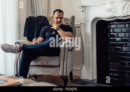 Mature man sitting in armchair by the fireplace in hotel room with a glass of whisky. Businessman staying in hotel during a business trip. - Stock Photo
