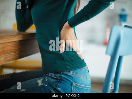 Woman with back pain sits on chair or office - Stock Photo