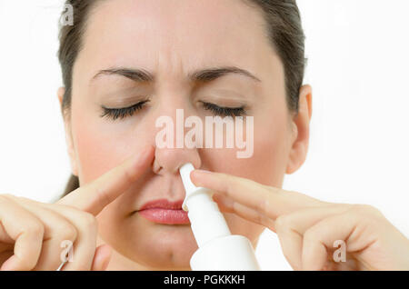 A young woman using nasal spray, covering nostril - Stock Photo