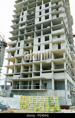 Low angle view at unfinished apartment building on construction site, copy space background - Stock Photo