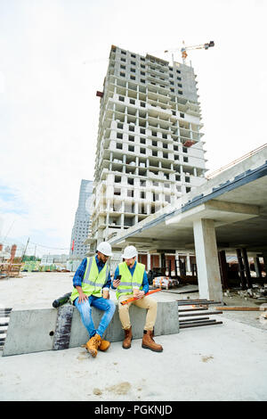 Wide angle portrait of two workers wearing hardhats  chatting and using smartphone during coffee break on construction site