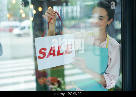 Waist up portrait of smiling female shopkeeper hanging SALE sign on door - Stock Photo