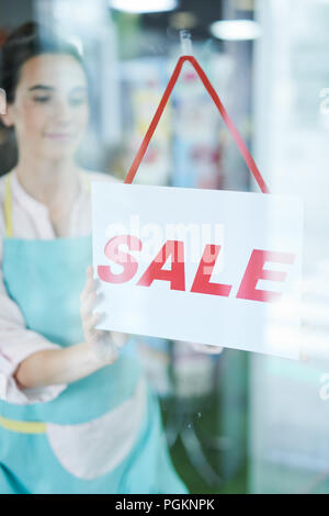 Portrait of smiling female shopkeeper hanging SALE sign on door - Stock Photo
