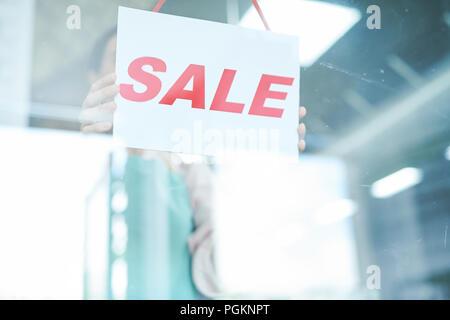 Portrait of shopkeeper hanging SALE sign on door, copy space - Stock Photo