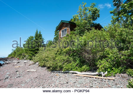 Cabin is perched on a low cliff with sweeping views of Lake Superior, near Grand Marais, Minnesota, USA. - Stock Photo