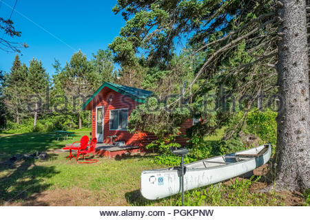 Canoe with electric motor is in front of a cabin located a short walk from Lake Superior, near Grand Marais, Minnesota, USA. - Stock Photo