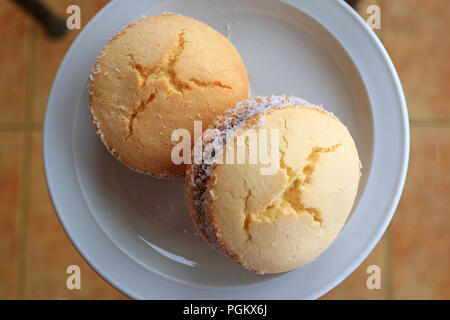 Top view of a pair of Alfajores, traditional Latin American sweets served on glass top table - Stock Photo
