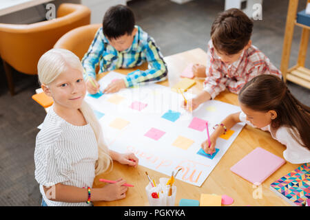 Pretty girl spending time with classmates at school - Stock Photo