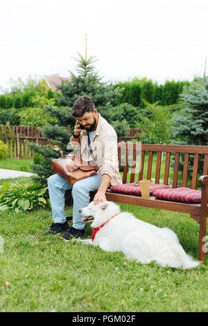 Dark-haired man playing with his white dog sitting on bench - Stock Photo