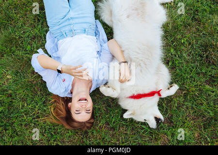 Funny woman laughing while playing with her white dog - Stock Photo