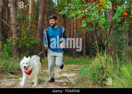 Bearded man wearing sport suit running with dog in the forest - Stock Photo