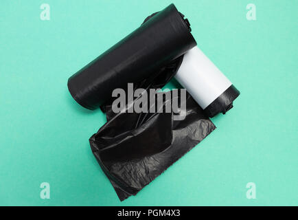 Black plastic rubbish garbage junk trash unused bag rolls as single use waste housework tool pollution recycling concept isolated on green background - Stock Photo