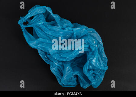 Old used crumpled blue shopping plastic or garbage bag as single use waste environment pollution concept isolated on black background - Stock Photo