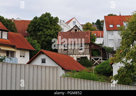 village with buildings at slope, tumbledown old hut in the middle of them - Stock Photo