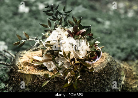 bouquet of flowers on a stump on the grass background - Stock Photo