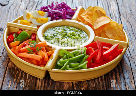 green salsa verde and mexican set of chopped fresh vegetables, hard boiled eggs  and chips in bowls on old rustic wooden board. ingredients for tacos, - Stock Photo