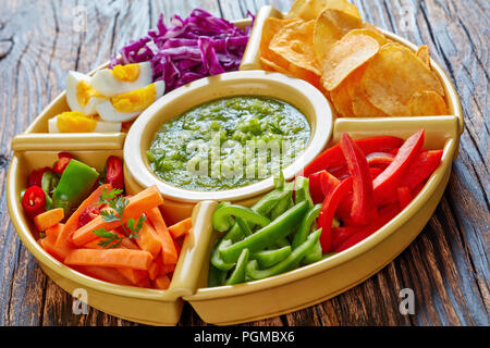 green salsa verde and mexican set of chopped fresh vegetables, hard boiled eggs and chips in bowls on old dark rustic wooden table. ingredients for ta - Stock Photo