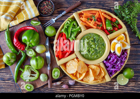 green salsa verde and mexican set for tacos consist of chopped fresh vegetables, hard boiled eggs and chips in bowls on old rustic wooden table with i - Stock Photo