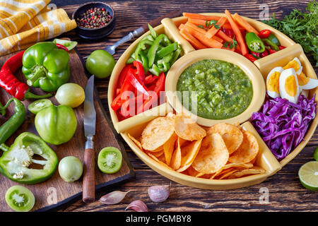 green salsa verde and mexican set of chopped fresh vegetables, hard boiled eggs and chips in bowls on old rustic wooden board with ingredients, view f - Stock Photo
