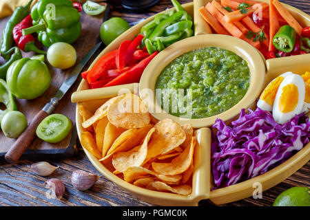 green salsa verde and mexican set of chopped fresh vegetables, hard boiled eggs and chips in bowls on old rustic wooden board with ingredients, horizo - Stock Photo