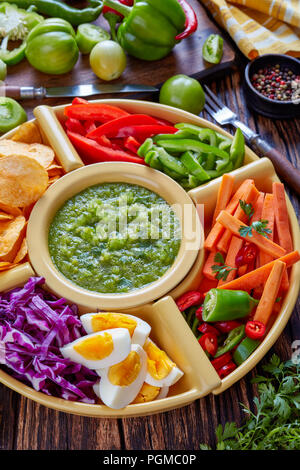 green salsa verde and mexican set of chopped fresh vegetables, hard boiled eggs and chips in bowls on old rustic wooden board with ingredients, vertic - Stock Photo