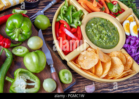 green salsa verde and mexican set of chopped fresh vegetables, hard boiled eggs and chips in bowls on old rustic wooden table with ingredients, horizo - Stock Photo