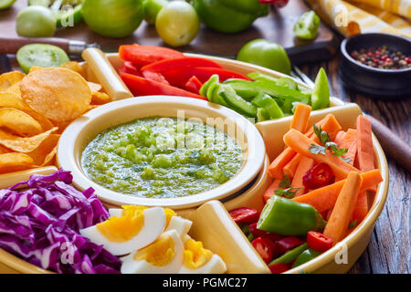 close-up of green salsa verde and mexican set for tacos consist of chopped fresh vegetables, hard boiled eggs and chips in bowls on old rustic wooden  - Stock Photo