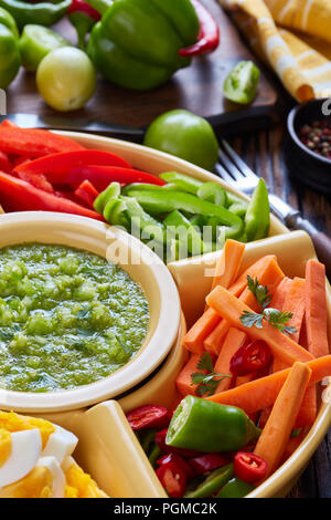 green salsa verde dipping and mexican set of chopped fresh vegetables, hard boiled eggs and chips in bowls on old rustic wooden table with ingredients - Stock Photo