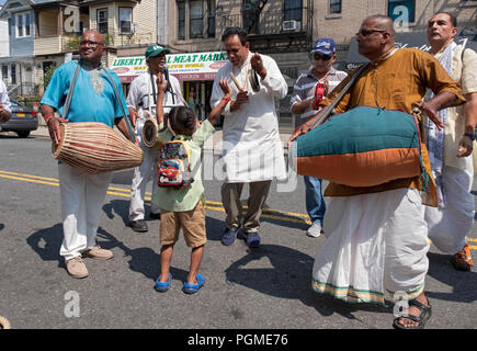 A young Hindu girl dances gleefully while musicians play before the 2018 Queens, New York rathayatra Parade.