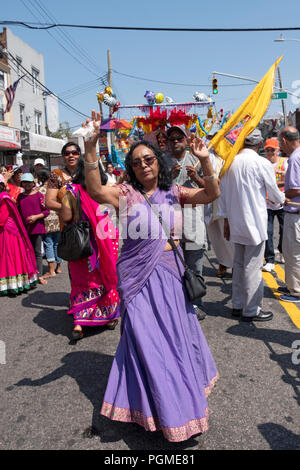 A woman in a beautiful sari happily marching at the Queens, New York Rathayatra Parade. - Stock Photo