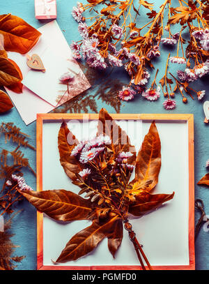 Autumn flowers bunch with orange leaves and chrysanthemum flowers on desktop background with decoration and florist tools - Stock Photo