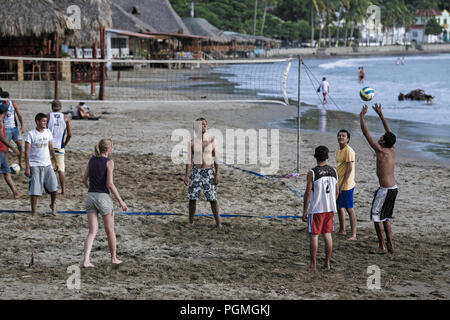 Tourists and locals playing game of beach volleyball in San Juan Del Sur, Nicaragua - Stock Photo
