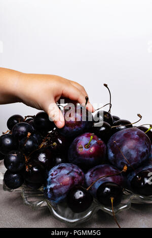 plate with fresh plum, grape, cherry and child hand. Fresh eating concept. Vegan food - Stock Photo