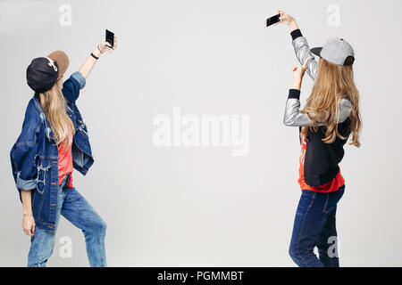 Two girls in stylish clothing taking selfie on smartphone. - Stock Photo