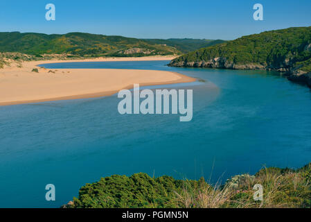 Beautiful river with turquoise water surrounded by sand banks and green hills - Stock Photo