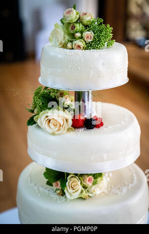 wedding cake decorated with berries and flowers - Stock Photo