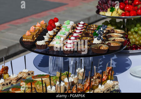 Catering service . sandwiches meat, fish, vegetable canapes on a festive wedding table outdoor - Stock Photo