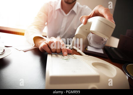 Businessman dialing a telephone number in order to make a phone call. - Stock Photo