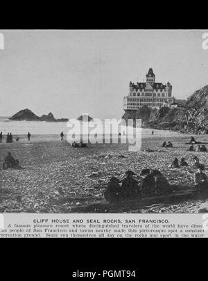 Black and white photograph showing people and seals sitting and standing on a beach in the foreground with the ocean, cliffs, and Adolph Sutro's late-19th-century Cliff House Restaurant, a multilevel Victorian Chateau, in the background, captioned 'Cliff House and Seal Rocks, San Francisco', 1906. Courtesy Internet Archive. () - Stock Photo