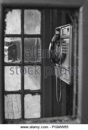 Broken phone box on a London street. This hasn't been used in years, though the phone itself seems to have survived the test of time. - Stock Photo