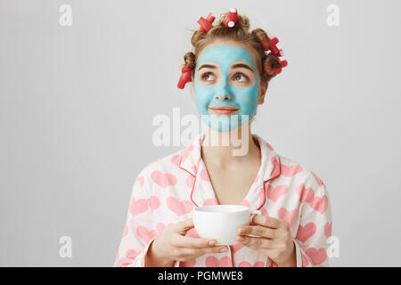 Dreamy cute european girlfriend in hair-curlers and pyjamas, standing in blue facial mask, holding cup of tea, smiling and looking aside, thinking about something positive. Girl enjoys quiet evening - Stock Photo