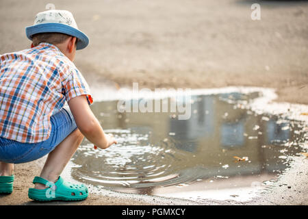 Children's outdoor play. sitting on his haunches near the large puddles. Summer - Stock Photo